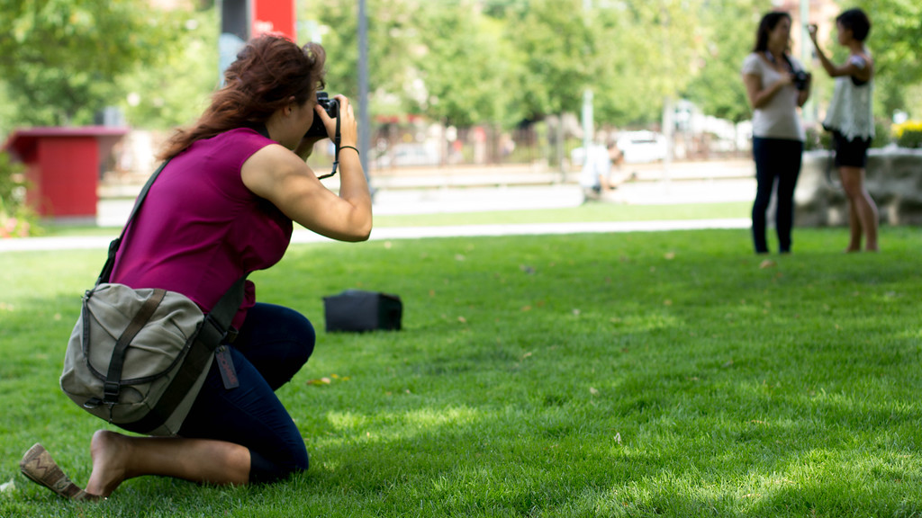 Lauren Westberg takes a photograph of two Boston University students in front of the COM building during a class project on Saturday.