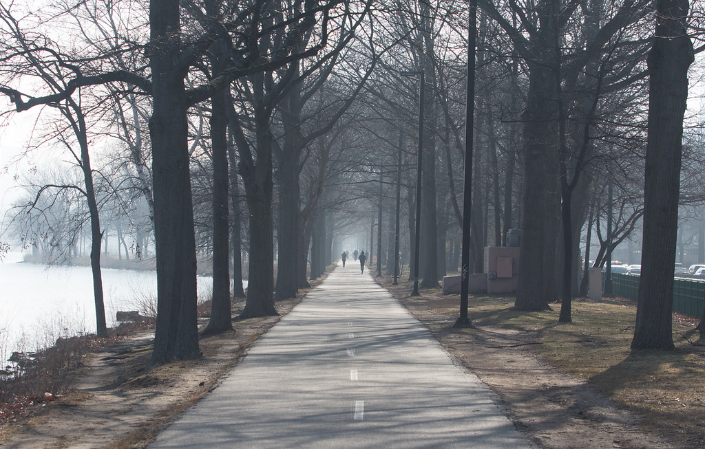 """Runners on the Charles River esplanade in early morning mist on April 11.  This image is part of  the 24-hour project """"Between the Bridges."""" Photo by: Lauren Fogelström"""