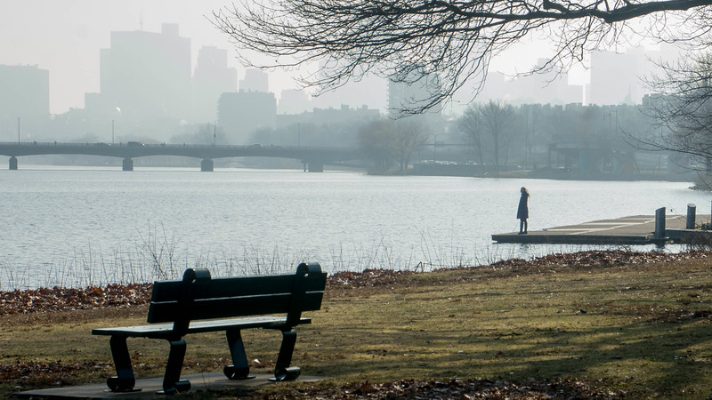 "A woman stands near the  Charles River Wednesday morning. This is a segment from the ""24 hours, two bridges"" project."