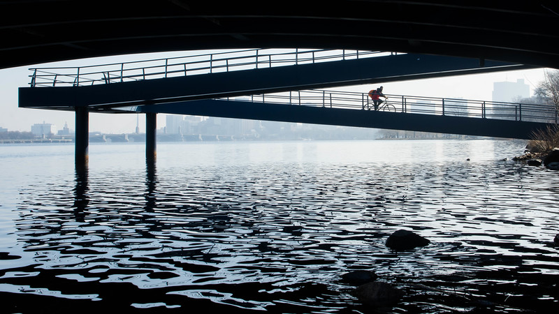 "A cyclist rides down the ramp from Massachusetts Ave. onto the Esplanade along the  Charles River Wednesday morning. This is a segment from the ""24 hours, two bridges"" project."