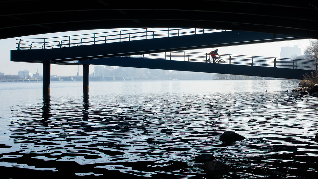 """A cyclist rides down the ramp from Massachusetts Ave. onto the Esplanade along the  Charles River Wednesday morning. This is a segment from the """"24 hours, two bridges"""" project."""