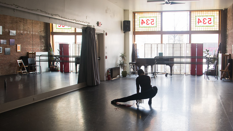Jo Troll stretches during rehearsal at the Dance Complex in Central Square, April 11.