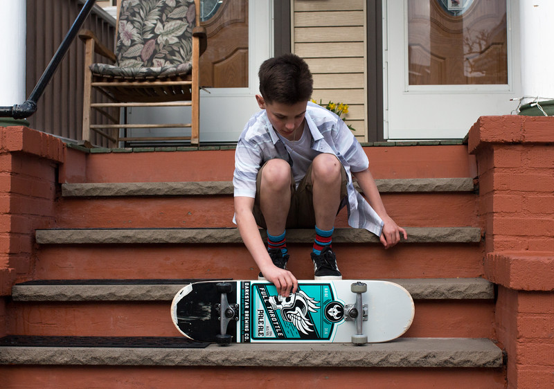 Jimmy takes a break from skakeboarding and leans his board on the steps of their house in Somerville on April 19.