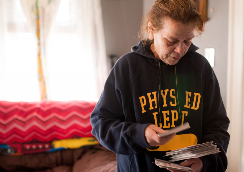 Judi Walker sifts through a stack of names each representing an individual who died of an opiod overdose, at her home in Somerville on April 13. Through SOA, she's helped to organize vigils for each of them, all of which she knew personally.