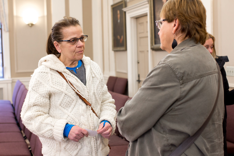 Judi Walker chats with a  member of CASPAR Inc., an organization dedicated to assisting individuals who struggle with substance abuse, before the community meeting on opiod use in Somerville, hosted by the Public Health and Public Safety department on April 10 at Somerville City Hall.