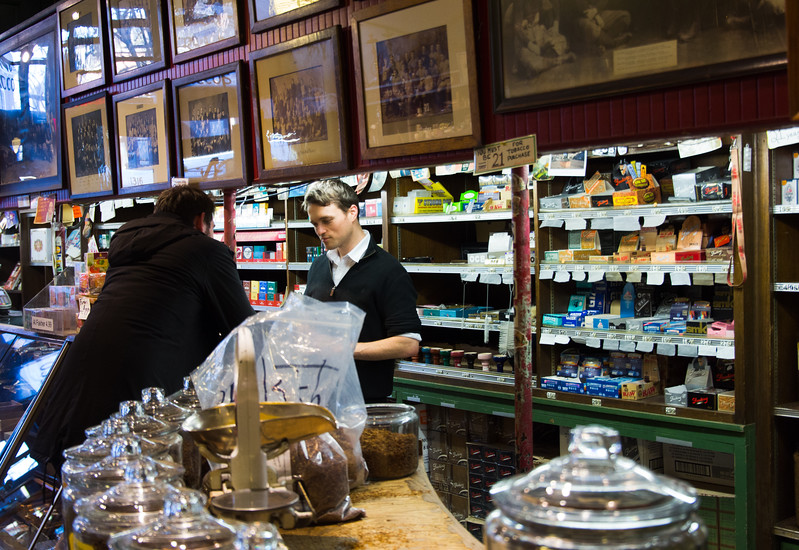 Employee Norris Duncan , 28, attends to a customer buying tobacco at Leavitt & Peirce Inc., in Harvard Square, Cambridge on Feb. 18. Since 1884, the store has sold a wide variety of tobacco, smoking supplies, games, vintage gifts and shaving tools.