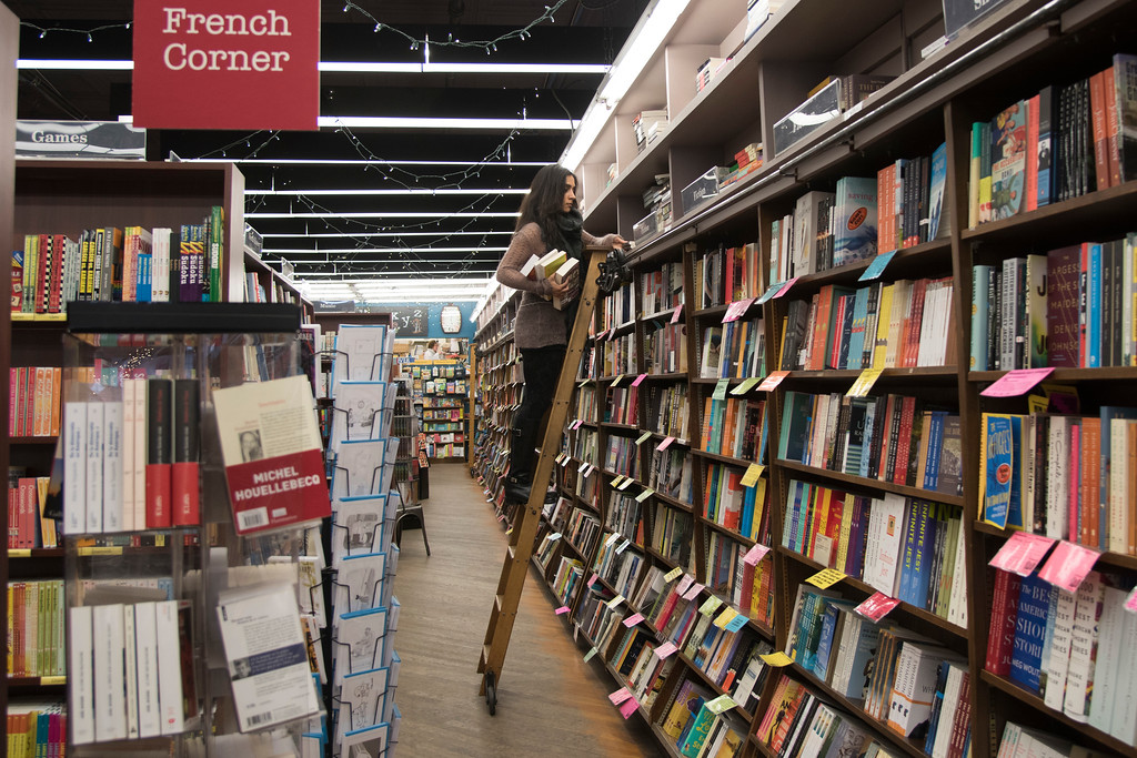 """Shuchi Saraswat, and employee of Brookline Booksmith in Coolidge Corner, re-shelves books during her shift on February 15. Brookline Booksmith, who's slogan is """"dedicated to the fine art of browsing,"""" has been a staple in the Brookline community since its founding in 1961."""