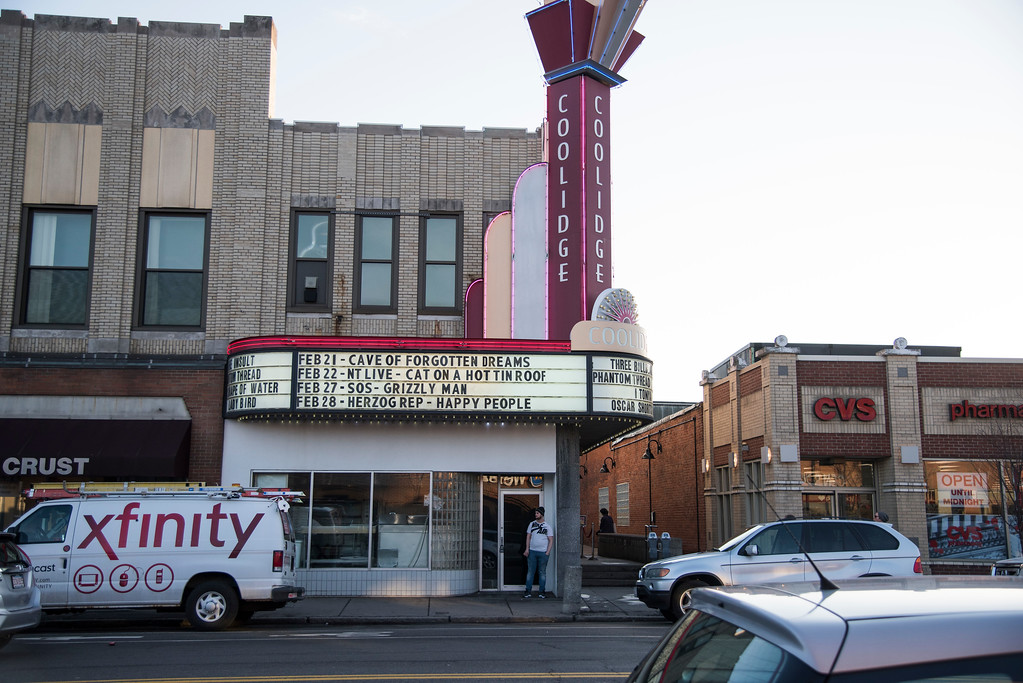 A man stands in front of the Coolidge Corner Theater, Brookline's first movie theater. Built in 1903 as a universalist church, it was converted into an Art Deco movie theater in 1933. Due to financial pressures and an inability to keep up with modern movie fads, the theater was sold to Harold Brown, a Boston real estate mogul, who then leased it to the non-profit Coolidge Corner Theater Foundation in 1989.
