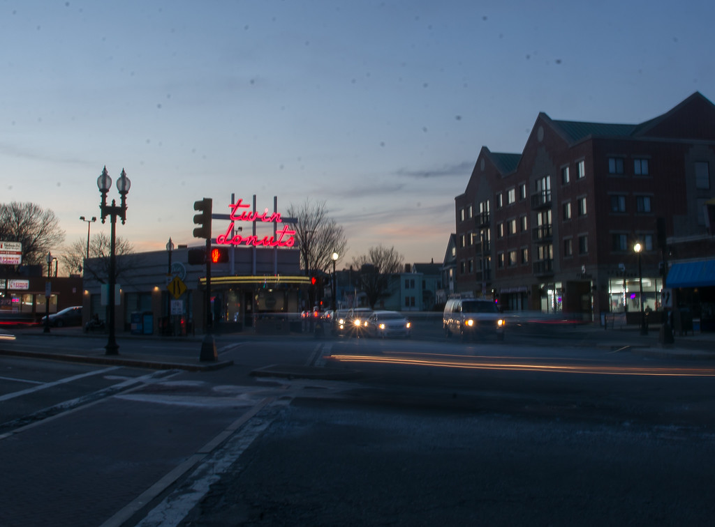 Car speed past Twin Doughnuts in Allston, Massachusetts.