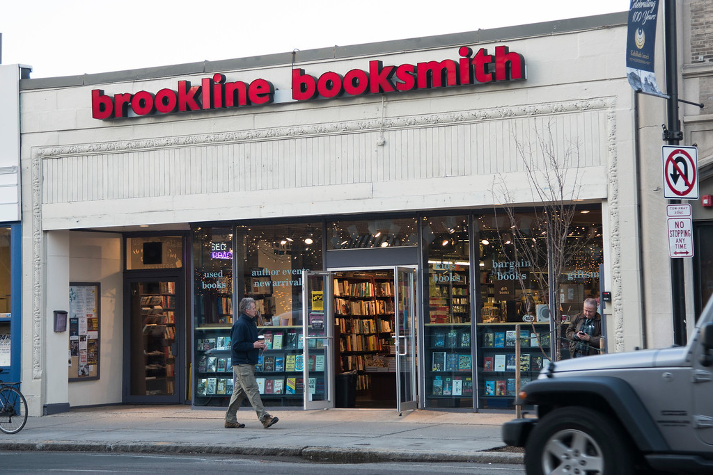 """A man walks past Brookline Booksmith, located in Coolidge Corner in Brookline.  The bookstore, who's slogan is """"dedicated to the fine art of browsing,"""" has been a staple in the Brookline community since its founding in 1961."""