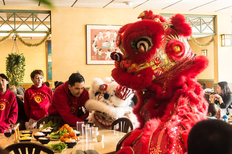 Instructor Lucien Zoll helps guide young performers through a Lion Dance Le's Vietnamese Cuisine in Allston. The dance is done as a celebration of the Lunar New Year to chase away bad spirits.