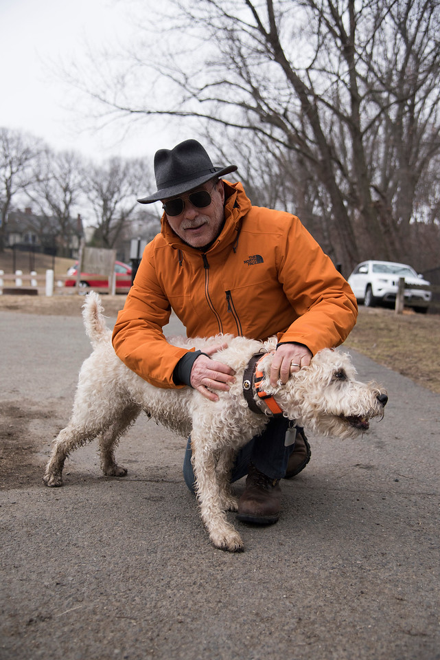 """Mike Gruben, a Brookline resident of 18 years, shows off the """"sherif badge"""" on his dog Randy's collar. """"Randy keeps the peace in the park with the other dogs,"""" said Gruben, """"when he's not too busy chasing them."""" Gruben has been walking his dog in Amory park almost every day for the last four years."""