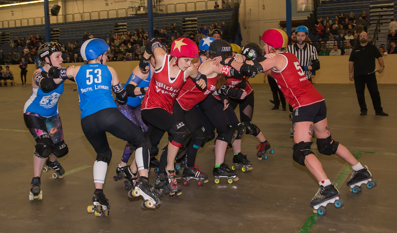 Wicked Pissah's Thunder Cat (center)pushes through a crowd of blockers to take the lead during a jam in during Boston Roller Derby's home bout.