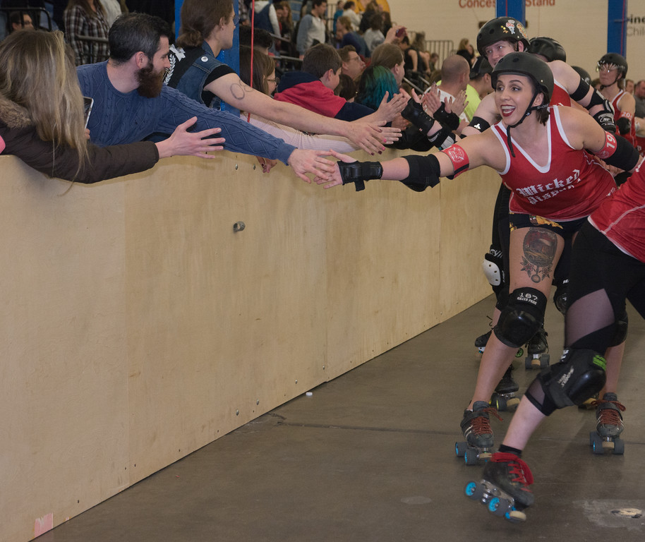 Wicked Pissah's high fives fans after the team's win against the Cosmonaughties during Boston Roller Derby's home bout.