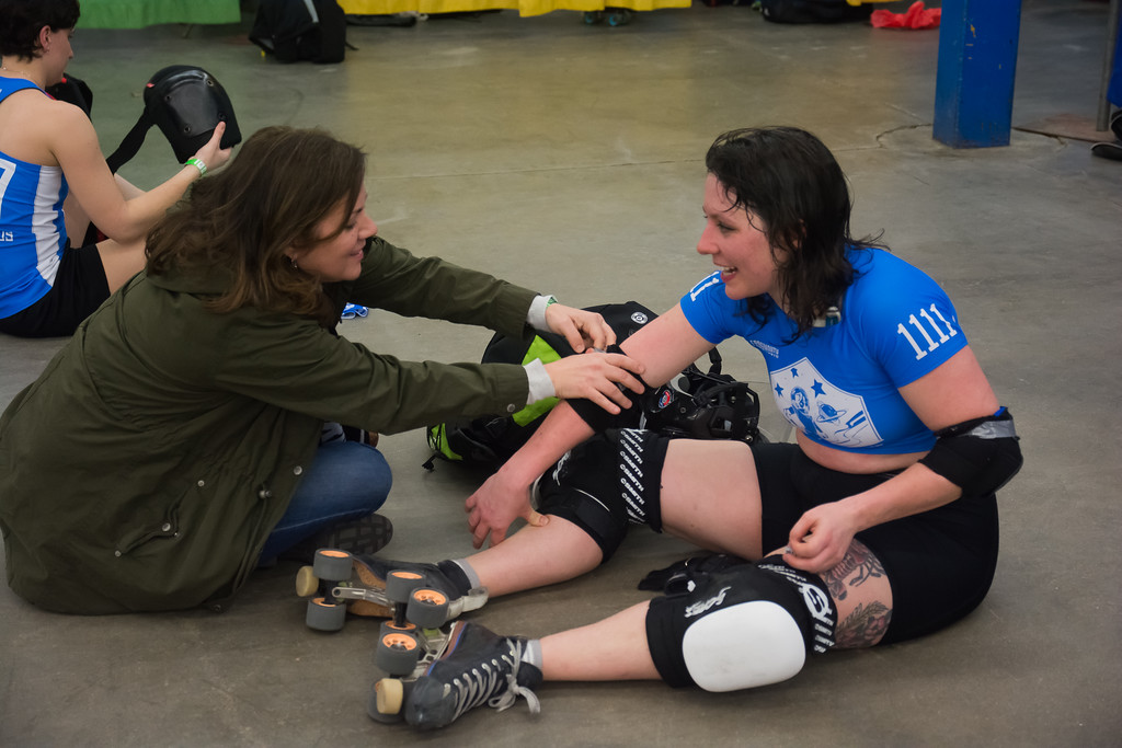 Allayne Sundt helps her daughter, Maya Mangleyou of the Cosmonaughties, remove her pads after a match against the Wicked Pissah's.