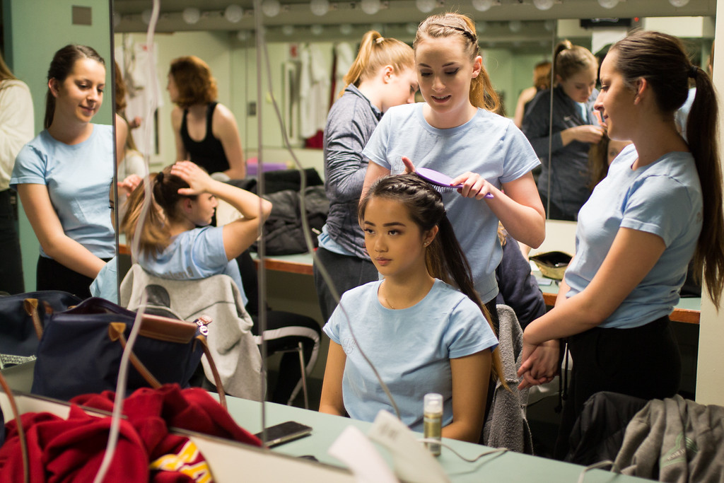 Dancer Lucy Yang, of the Boston University Edge team, has her hair braided by a teammate in preparation for their show at the Tsai Performance Center in Boston, on Feb. 24.