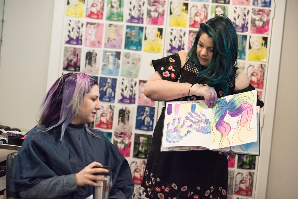 """Stephanie Geib, a hair dye specialist at Dellaria Salon, shows off her """"sketchbook"""" where she tests color combinations to client Sarah Lodato. """"This one is you!"""" said Geib, referring to her sketch of the colors in Lodato's hair. Geib, who has over 45k followers on instagram, is known for her vivid hairstyles and expert balayage, as well as her friendly and jovial nature."""