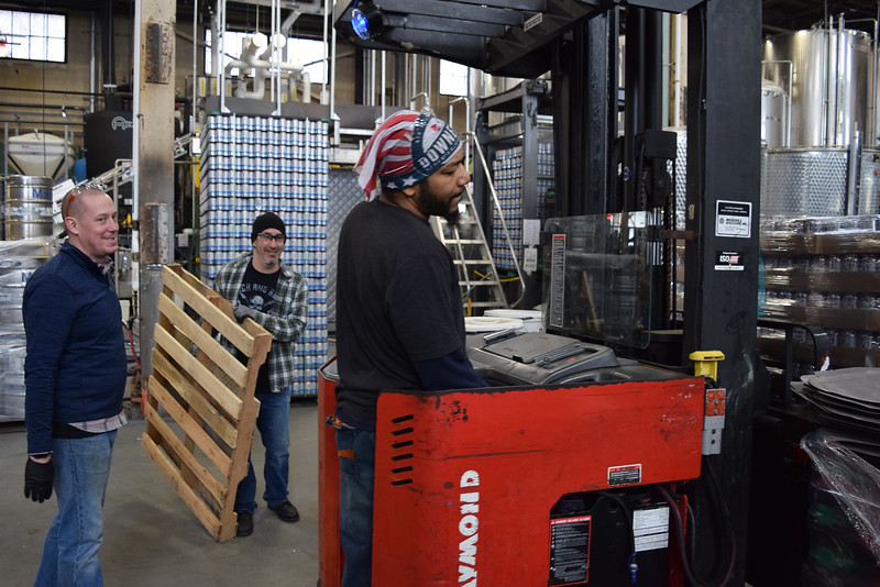 Jarrod Goyette and Adam Greenberg look on as coworker moves palates at Downeast cider house.