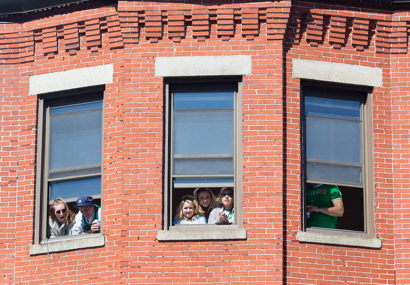 Viewers watch the first few floats from windows facing the street, during the 2018 St. Patricks Day parade on March 18 in South Boston.