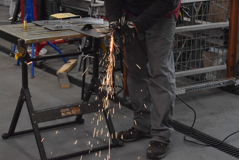 Vladimir Fris sends sparks flying as he files down a metal piece.