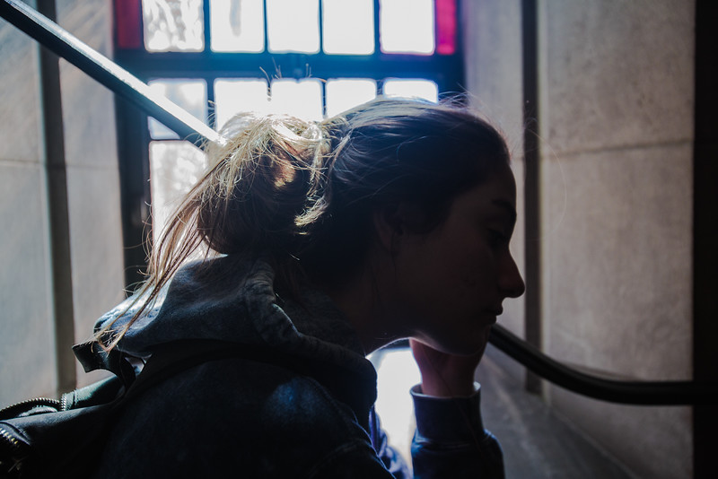Faith Allen, a transfer student studying pre-med, is sitting by a stained-glass window at Marsh Chapel,trying to figure out whether or not to believe in god.