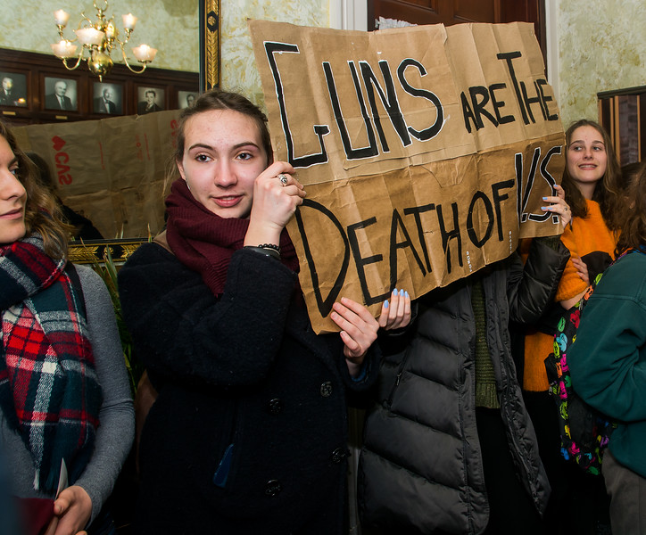 Elektra Manolakos displays a sign stating 'Guns are the death of U.S.' during a student visit to the Senate President's office at the Massachussetts State House. The visit took place as a part of the Walkout for Action on March 14.