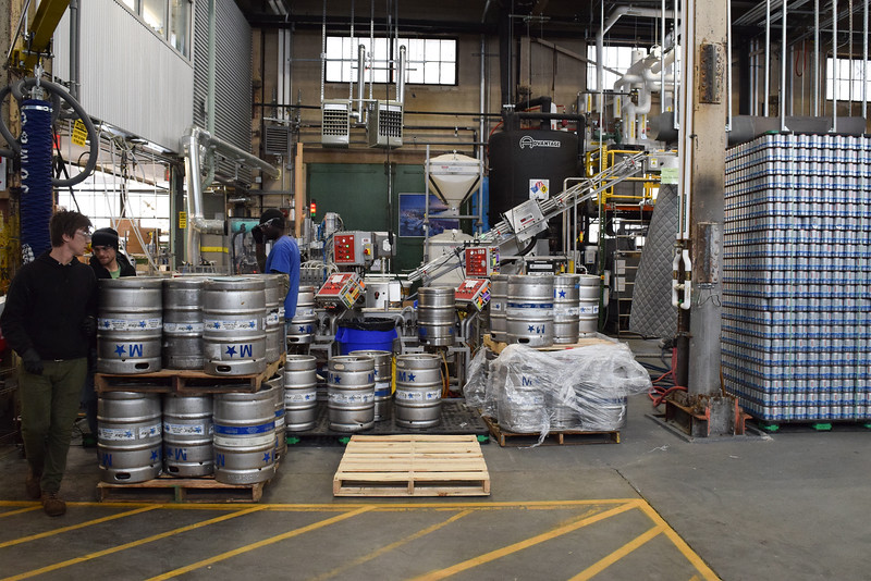 Jake Hennessey,  Jake Gavin and Nile Jones (seen left to right) move kegs to palates to be shipped. These three employees consist of about 60 that work at Downeast cider house in East Boston.