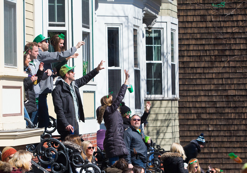 Viewers catch necklaces and candy thrown from parade floats during the 2018 St. Patrick's Day parade on March 18 in South Boston.