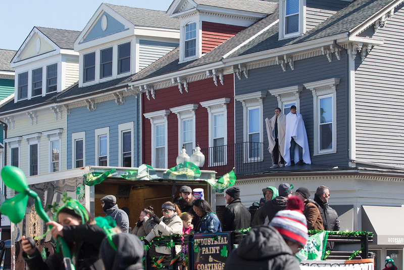 Viewers watch floats go by from their rooftop during the St. Patrick's Day parade, on March 18 in South Boston.