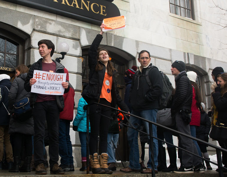 Emily Weinberg, a sophmore at Lexington High School, cheers as protestors enter the Massachusetts State House during the Walkout for Action on March 14. Next to her Zack Steigerwald Schnall, a freshman at Harvard, holds a sign demanding policy chnage over declarations of thoughts and preayers.