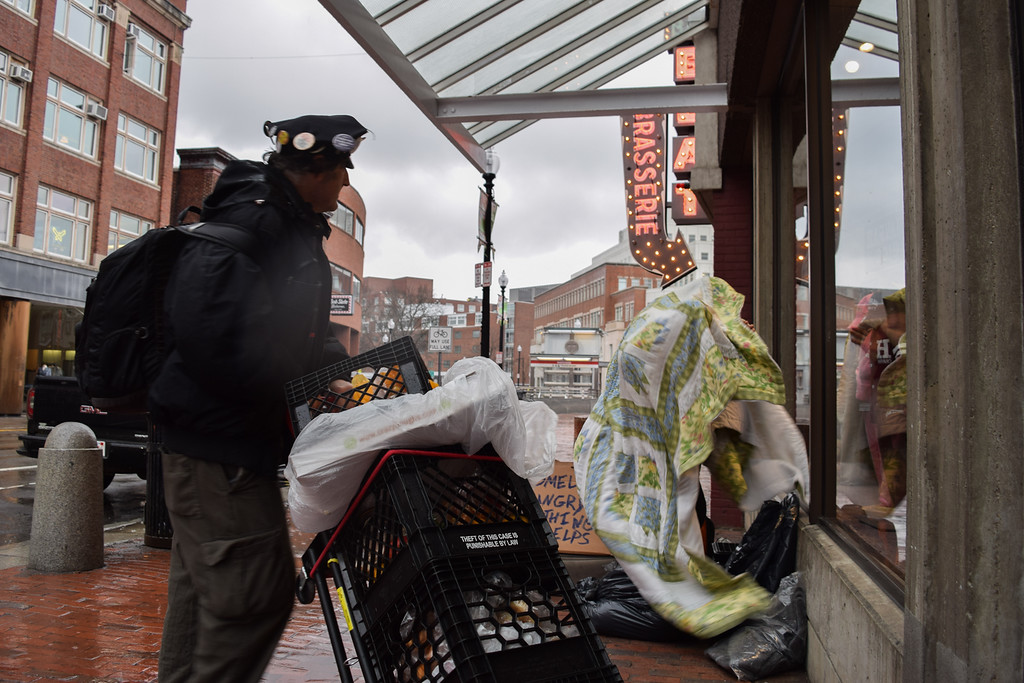 Harvard Square is an area with a prevalent homeless community which Kontoff delivers food to on a daily basis. The man seen wraps himself in a quilt to endure the elements, lacking in basic neccesities such as shoes and socks.