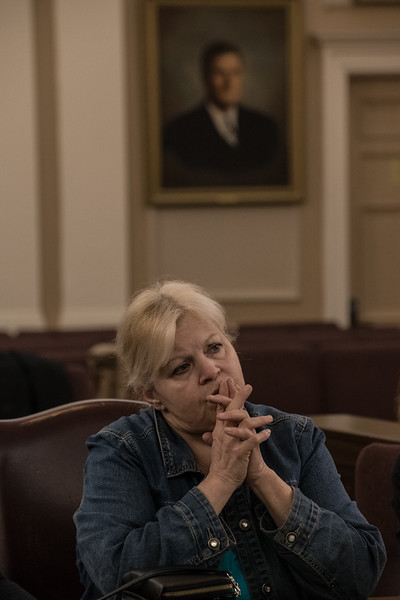 Joann attends a meeting in Somerville's Main Chamber Hall regarding Somerville's response to the opiod crisis. The actions discussed included training library staff to use Narcan, screening 10th graders at the local high school and installing dropboxes for prescription drugs. Behind her are portraits of two of Somerville's mayors from the World War II era. (Photo by: Billy Bevevino)