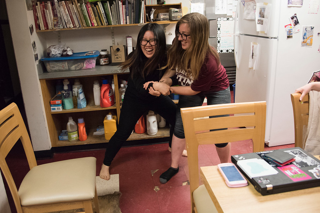 Ningyin Zhao and Rachel Poppe, both juniors at Boston University and both members of the Kung Fu team, demonstrate their moves in the HER House kitchen before leaving for practice.
