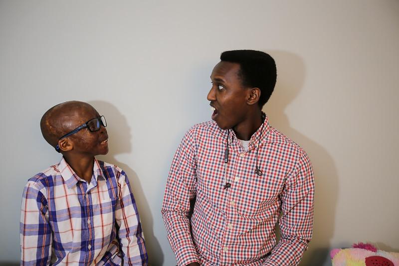 Leo Ikoribitangaza and Alex Gitungano sitting on bed.