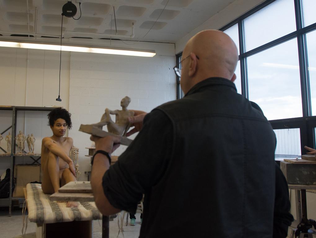Professor Batu Siharulidze compares a scuplture to Model Emily Jaques' pose during a studio class at Boston University's College of Fine Arts.