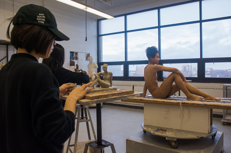Emily Jaques models for a sculpture studio class at Boston University's College of Fine Arts as Abbie Zheng works on a sculpture of her.