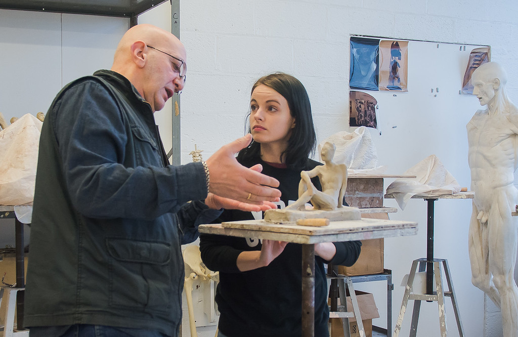 Professor Batu Siharulidze works with Kylie Moses on her sculpture during a studio class at Boston University's College of Fine Arts.