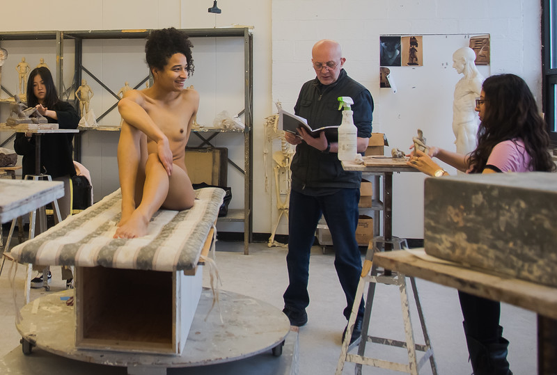 Emily Jaques jokes with Professor Batu Siharulidze while modeling for a sculpture studio class at Boston University's College of Fine Arts as students  work on sculptures of her.