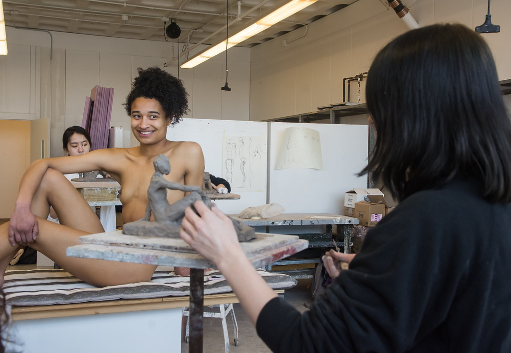Model Emily Jaques helps Kylie Moses with her sculpture during a studio class at Boston University's College of Fine Arts.