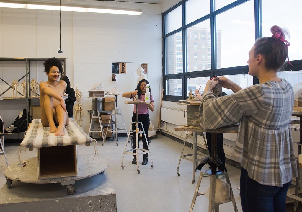 Emily Jaques models for a sculpture studio class at Boston University's College of Fine Arts as Evelyn Castro (left) and Samantha Morse work on sculptures of her.