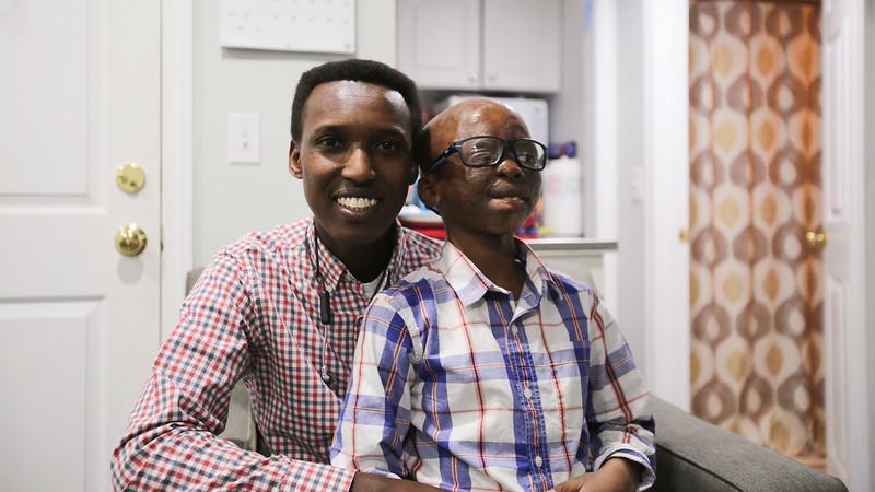 Alex Gitungano sitting with Leo Ikoribitangaza.