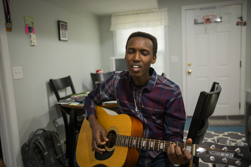 In a small but warm living room in Framingham, Alex Gitungano is playing his new song. Alex is now a graduate student at Boston University Medical School. This is his fourth year in the United States as a volunteer, helping a little boy, Leo Ikoribitangaza.