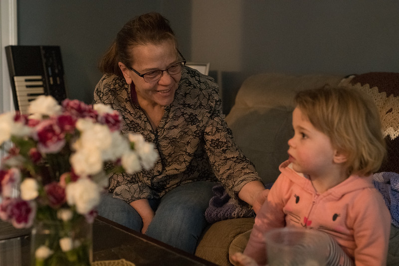 Judi coddles her niece at her home in Somerville as she is entranced by the TV. (Photo by Billy Bevevino)