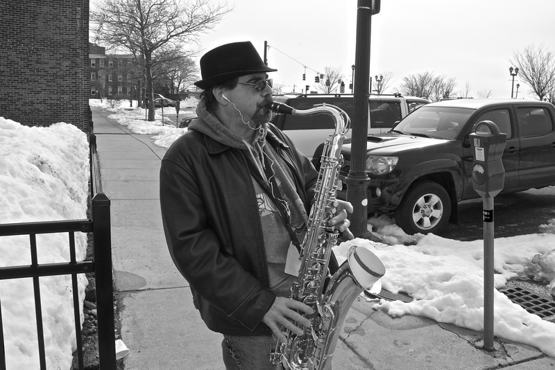 """Saxophonist Joseph """"Joe Sax"""" Cotreau Jr. entertains passers-by with his music on the sidewalks of Washington St., Salem, MA on a brisk, overcast Monday, March 11, 2013. Joe Sax is a well-known licensed street performer in the City of Salem. Photo by Michaela Vernava."""