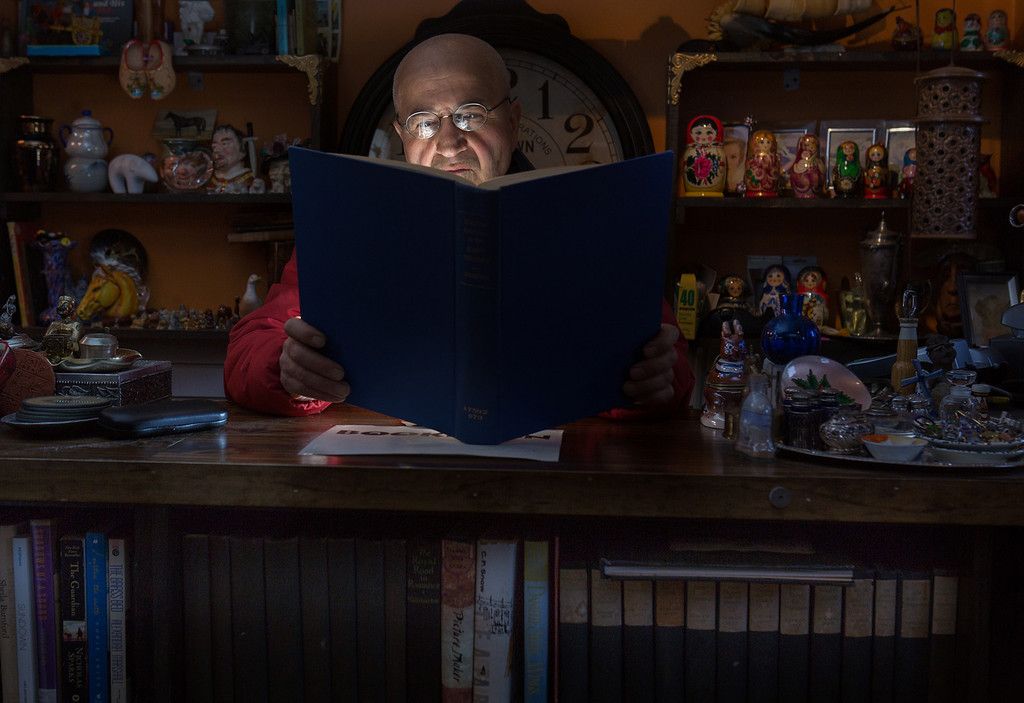 March 4, 2014 -- El-Cei, an immigrant from Iran, poses with a book from his collection at Tom Sawyer Books, a store he owns in Allston, Mass.