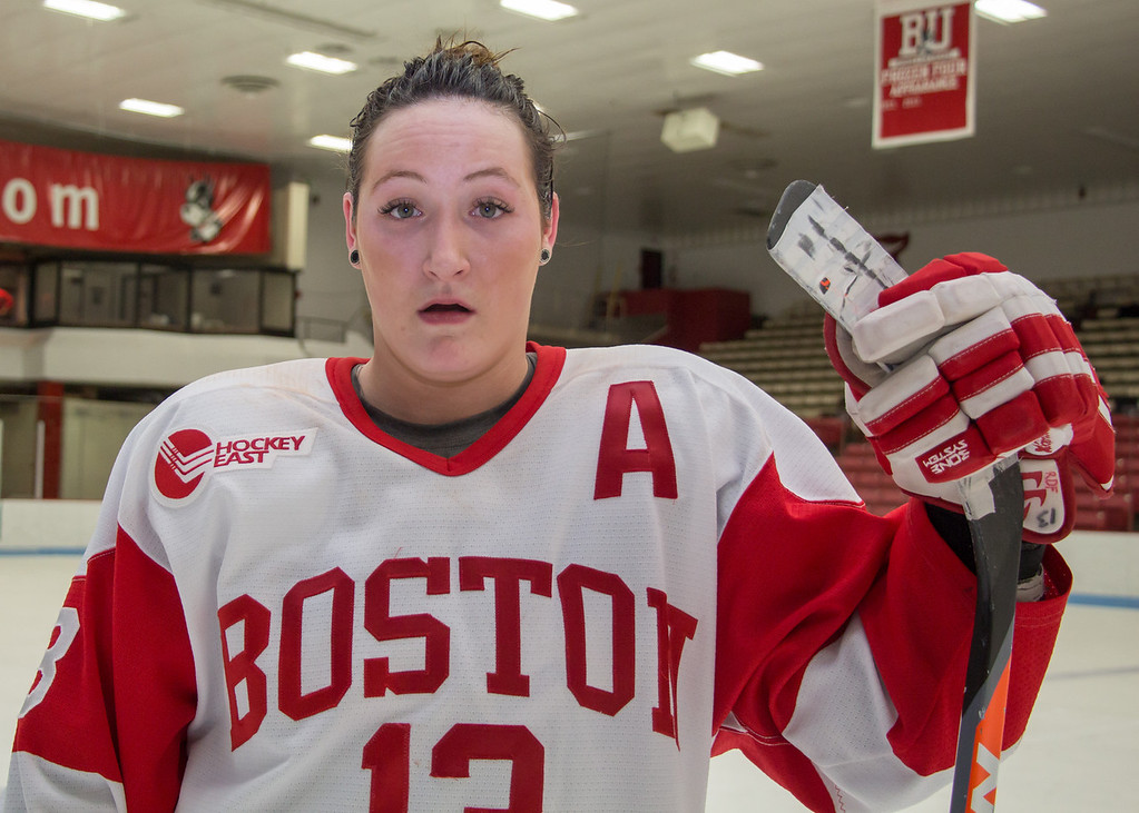 Boston, March 1, 2014 -- Boston University senior and women's hockey defense poses for a portrait in BU's Walter Brown Arena, after the team won the East Quarterfinals against Providence College. Photograph by Carolyn Bick. © Carolyn Bick 2014