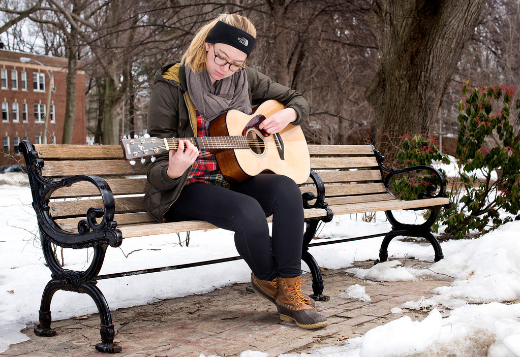 """March 4, 2014 –Boston, Mass. Emma Ransom plays guitar in Knyvet Square where she has played every week for the past four years. """"In the summer I get to enjoy playing in the sun for a lot of people and in the winter I get to play in solitude and really just focus on my music,"""" she says. Photo by Mackenzie Wiler."""