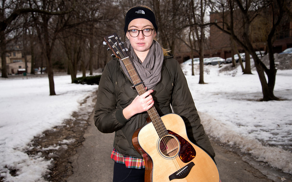 """March 4, 2014 –Boston, Mass. Emma Ransom poses with her guitar in Knyvet Square where she has played every week for the past four years. """"In the summer I get to enjoy playing in the sun for a lot of people and in the winter I get to play in solitude and really just focus on my music,"""" she says. Photo by Mackenzie Wiler."""