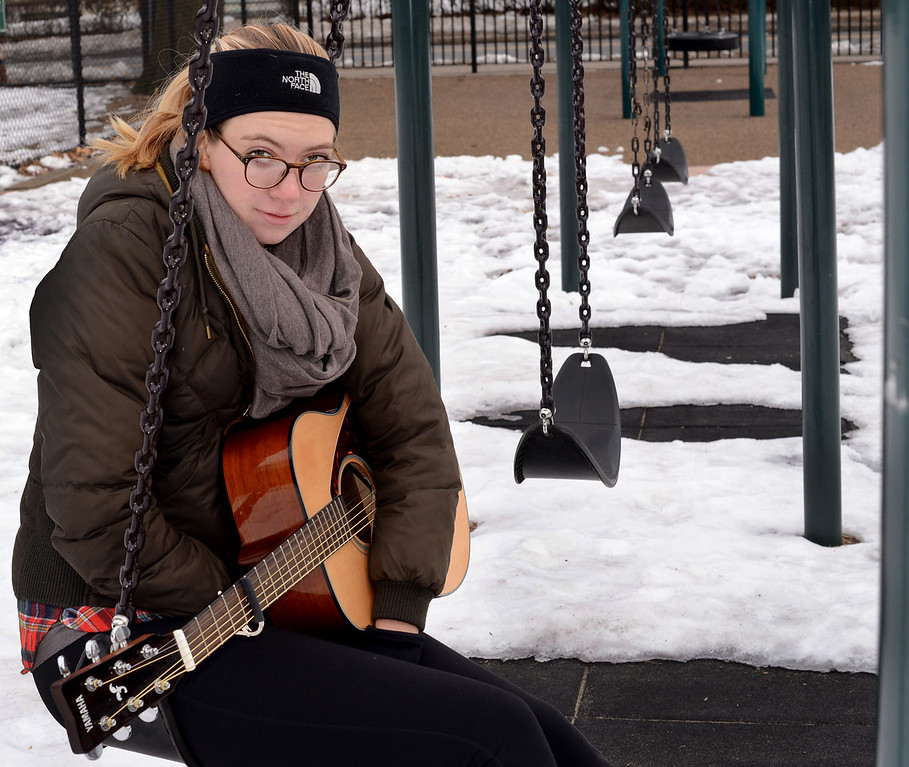 """March 4, 2014 –Boston, Mass. Emma Ransom takes a break from playing guitar in Knyvet Square and warms up her hands across the street on a swing set at Winthrop Square. Emma played for two hours with the outside temperature at 22 degrees. """"In the summer I get to enjoy playing in the sun for a lot of people and in the winter I get to play in solitude and really just focus on my music,"""" she says. Photo by Mackenzie Wiler."""