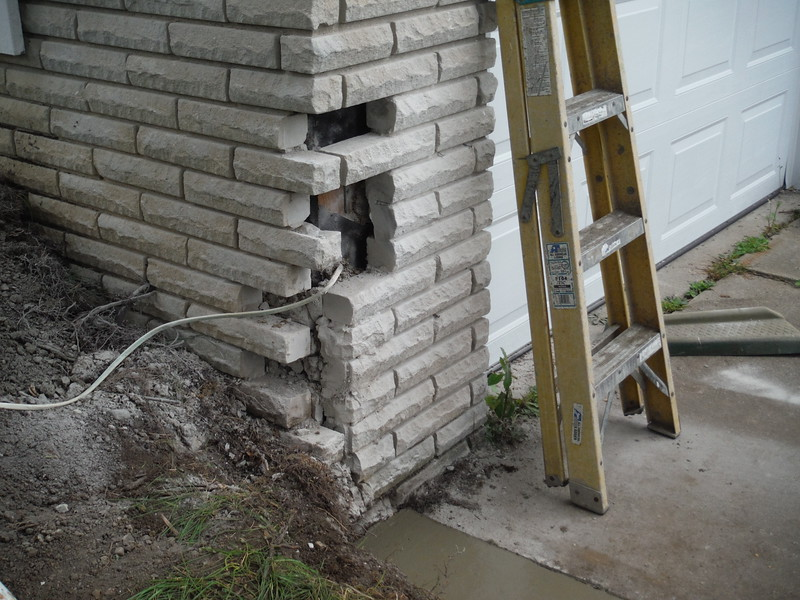 All cracked brick in garage wall are torn out.